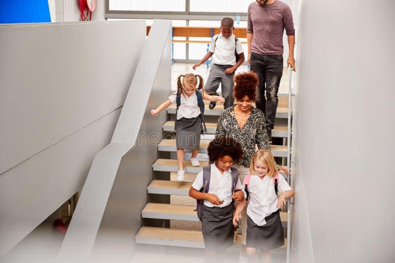 Profesor And Pupils Walking abajo de las escaleras en pasillo ocupado de la escuela primaria imágenes de archivo libres de regalías