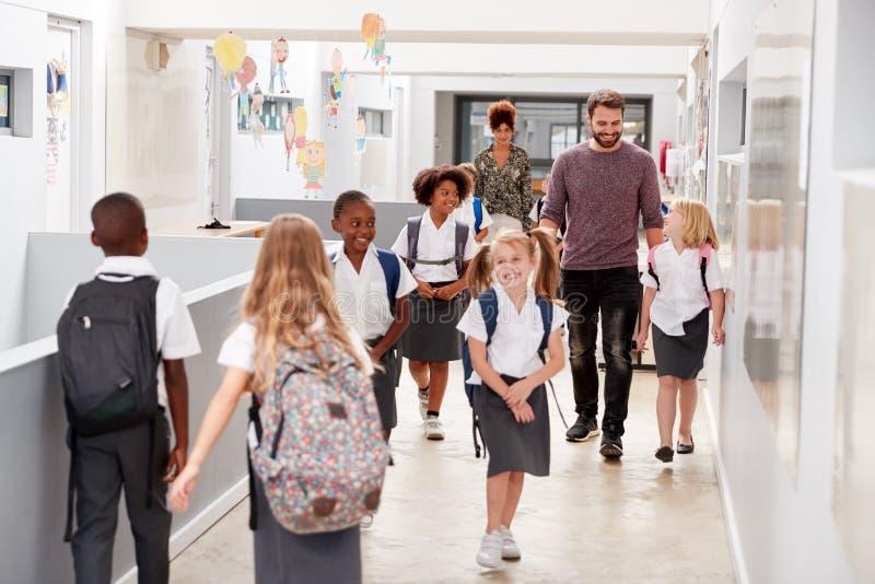 Profesor And Pupils Walking a lo largo del pasillo en pasillo ocupado de la escuela primaria imágenes de archivo libres de regalías