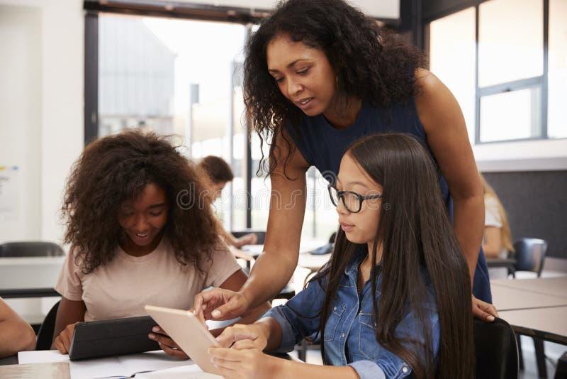 Profesor que ayuda a estudiantes de la High School secundaria con tecnología foto de archivo