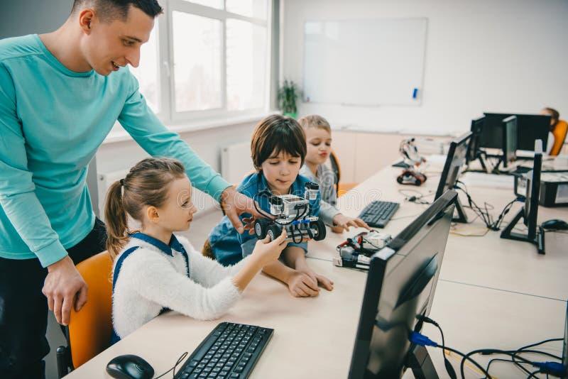 profesor que ayuda a sus estudiantes adolescentes con el robot diy en tronco foto de archivo libre de regalías
