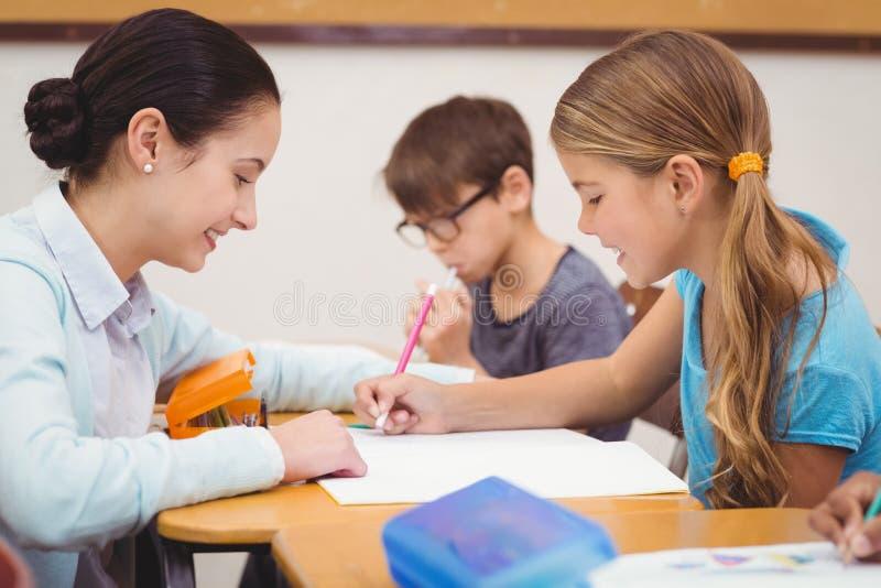 Profesor que ayuda a una niña durante clase imagen de archivo