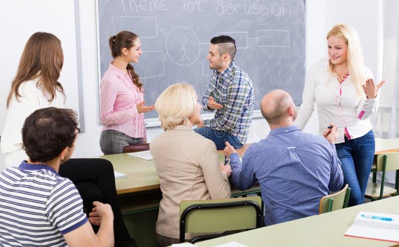 Profesor que consulta a diversos estudiantes de la edad imagenes de archivo