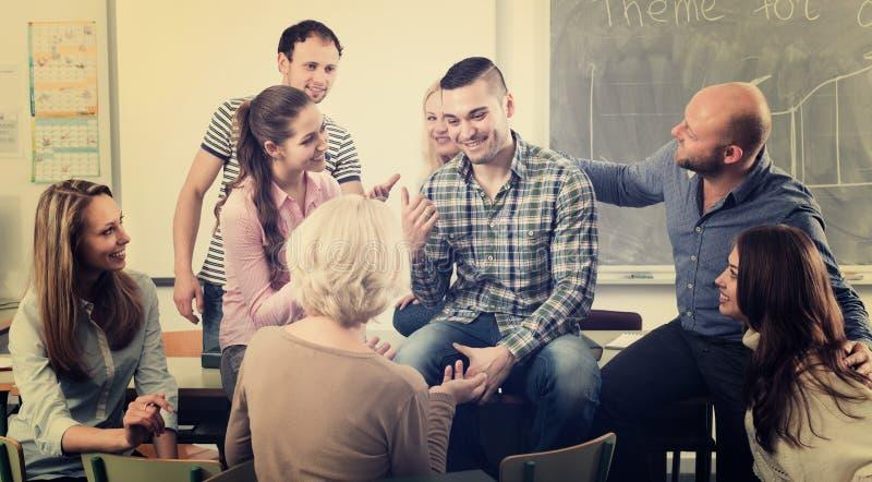 Profesor que consulta a diversos estudiantes de la edad fotos de archivo