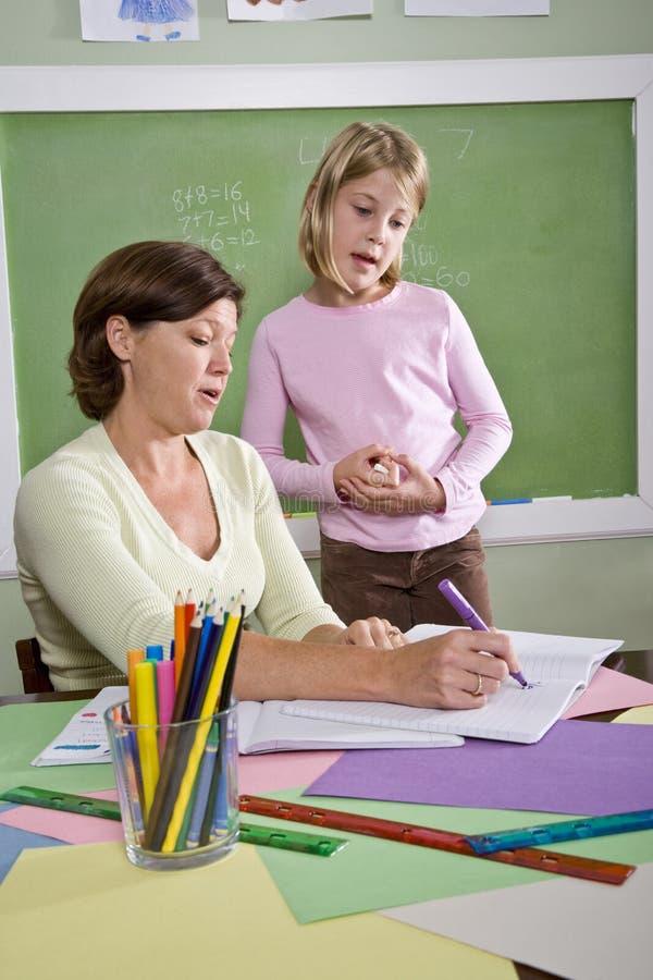 Profesor que enseña al estudiante joven en sala de clase imagenes de archivo