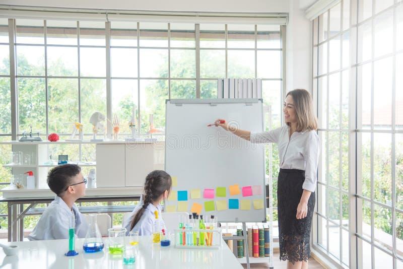 Profesor que escribe al tablero blanco, estudiante de enseñanza en sala de clase imagenes de archivo