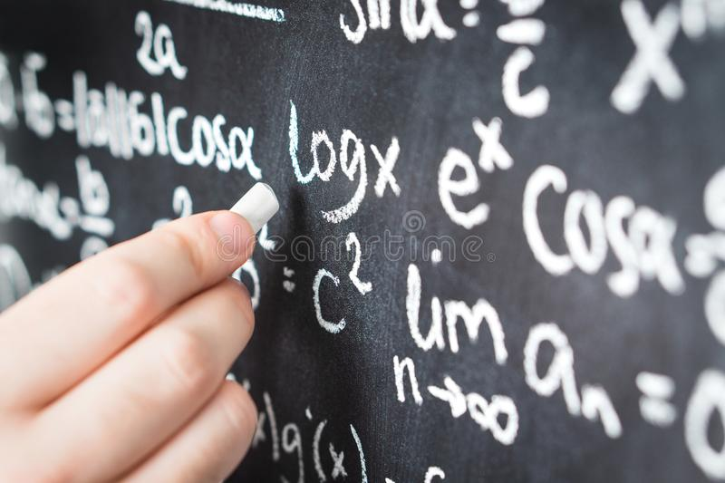 Profesor que escribe fórmula matemática y la ecuación fotos de archivo