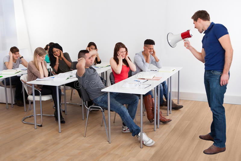 Profesor que grita a través del megáfono en estudiantes universitarios fotos de archivo