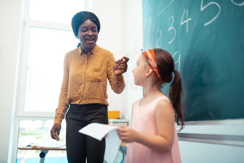 Profesor que habla con la situación de la muchacha cerca de la pizarra imagen de archivo