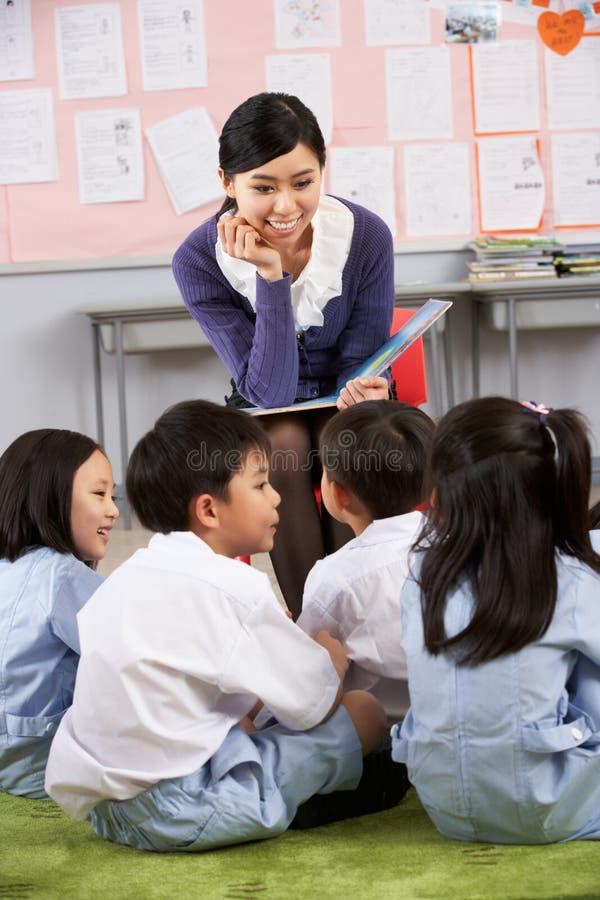 Profesor que lee a los estudiantes en escuela china imagenes de archivo