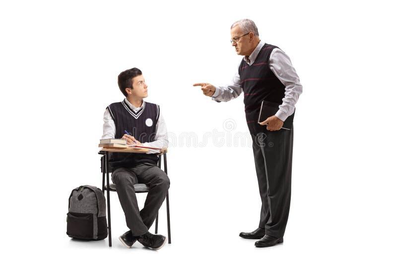 Profesor que regaña a un estudiante adolescente asentado en una silla de la escuela fotos de archivo libres de regalías