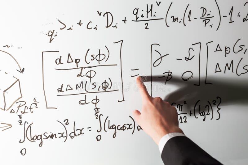 Profesor que señala el finger en símbolo de la matemáticas de la igualdad en whiteboard Matemáticas y ciencia fotografía de archivo libre de regalías