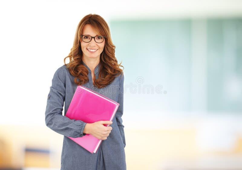 Profesor que se coloca con el cuaderno en sala de clase fotos de archivo libres de regalías