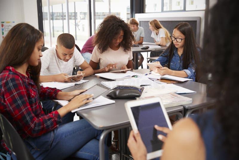 Profesor que se sienta con los estudiantes de la High School secundaria que usan las tabletas foto de archivo
