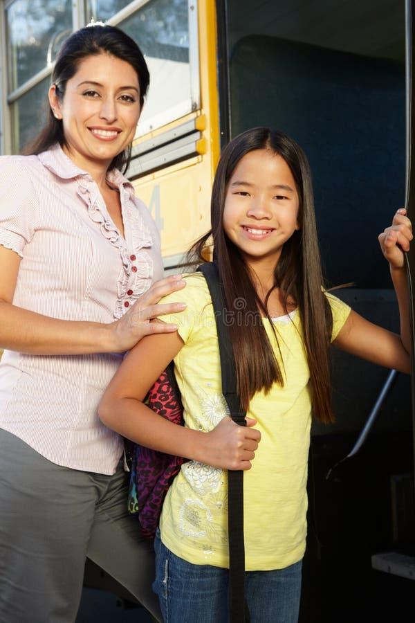 Profesor que ve la pupila sobre el autobús escolar fotos de archivo