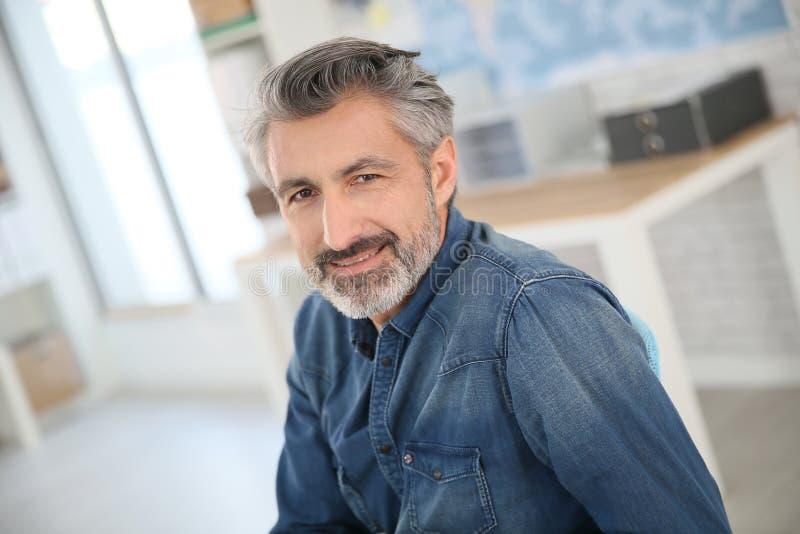 Profesor sonriente que se sienta en el escritorio foto de archivo libre de regalías