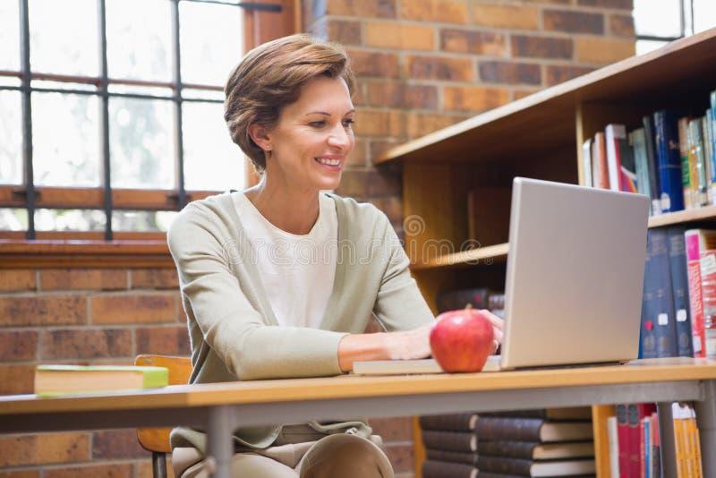 Profesor sonriente que usa el ordenador portátil en un escritorio imagenes de archivo