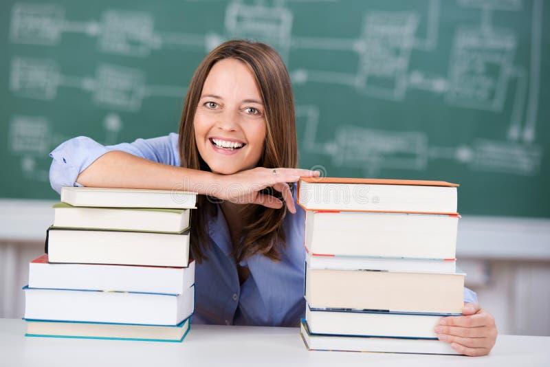 Profesor sonriente With Two Stack de libros en el escritorio foto de archivo libre de regalías