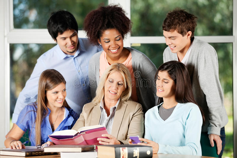 Profesor And Students Discussing sobre el libro adentro imagen de archivo