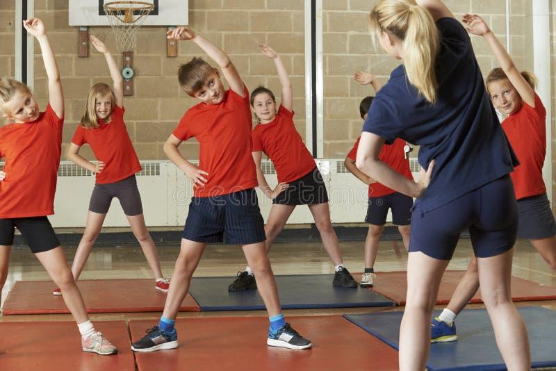Profesor Taking Exercise Class en gimnasio de la escuela imágenes de archivo libres de regalías