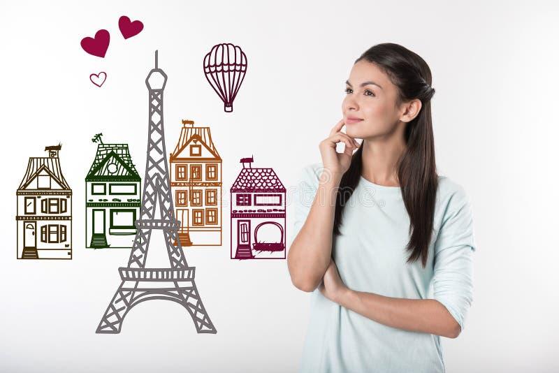 Profesor tranquilo que sonríe mientras que sueña sobre París imagenes de archivo