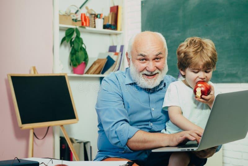 Profesor y alumno que aprenden junto en escuela Un abuelo y un niño están aprendiendo en clase Estudiante y clases particulares imagen de archivo libre de regalías