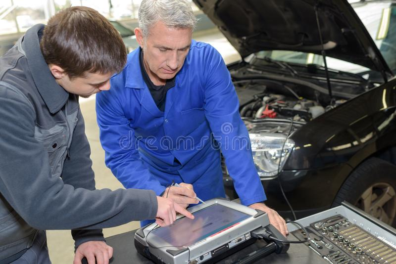 Profesor y aprendiz del mecánico de automóviles que realizan pruebas en la escuela del mecánico imagen de archivo