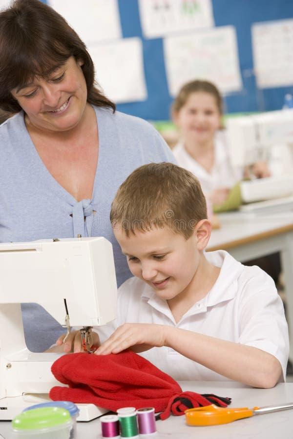 Profesor y colegial que usa una máquina de coser imágenes de archivo libres de regalías