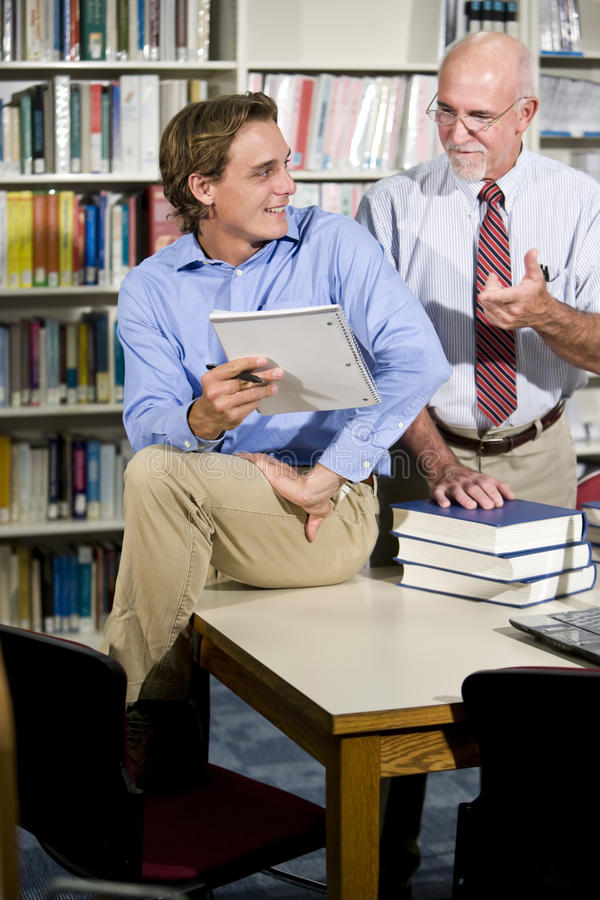 Profesor y estudiante de la universidad que hablan en biblioteca foto de archivo