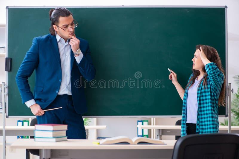 Profesor y estudiante hermosos jovenes en la sala de clase fotos de archivo libres de regalías