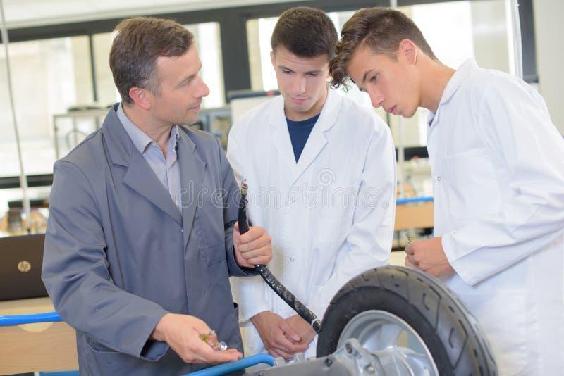 Profesor y estudiantes que miran la rueda fotografía de archivo