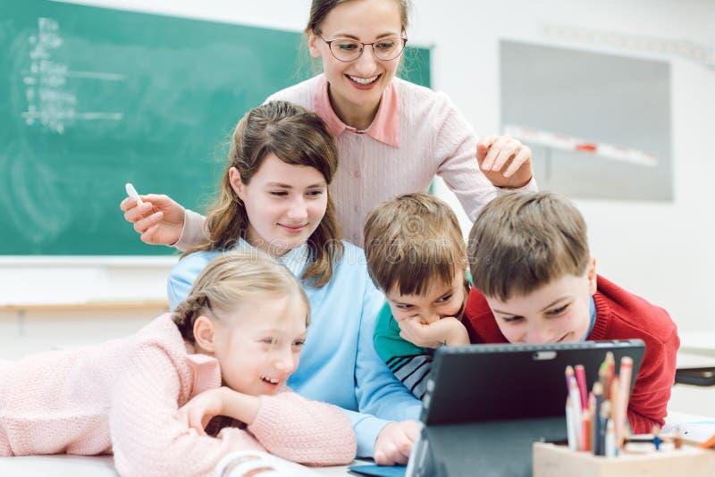 Profesor y estudiantes que usan medios y tecnología en sala de clase fotos de archivo
