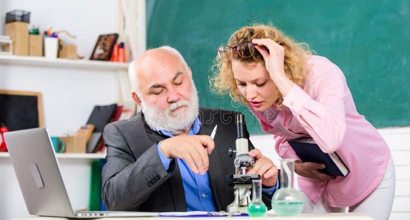 Profesor y muchacha con la libreta cerca de la pizarra Ciencia de la biolog?a Biolog?a del estudio Educación de la universidad de foto de archivo libre de regalías