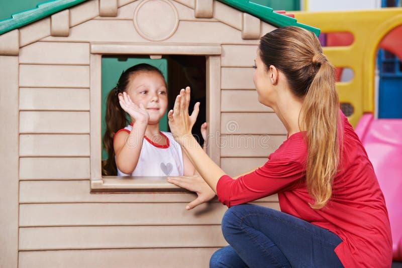 Profesor y muchacha del cuarto de niños que juegan al juego que aplaude imagen de archivo libre de regalías