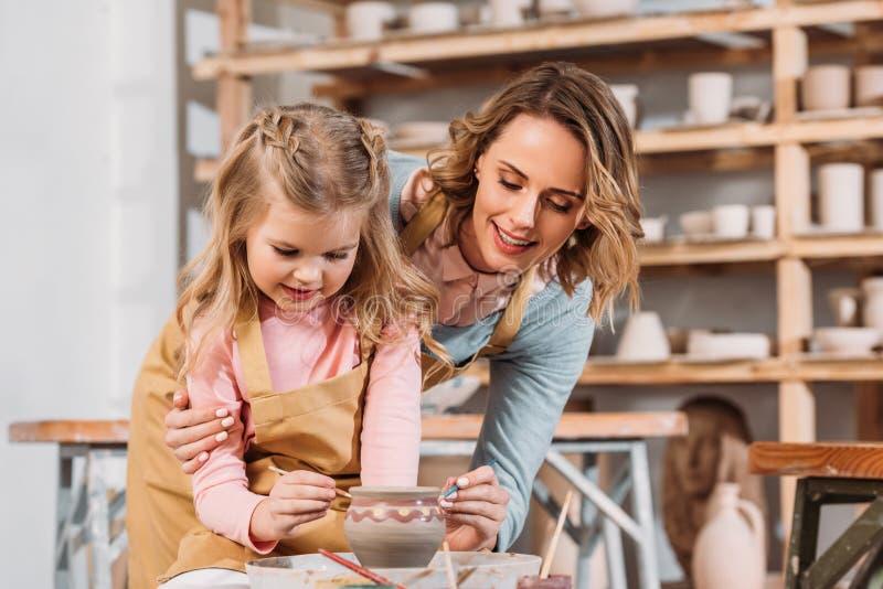 profesor y niño que pintan el pote de cerámica imagenes de archivo