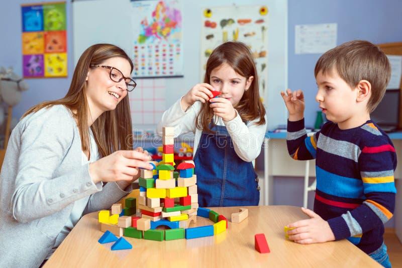 Profesor y niños así como bloques coloridos del juguete del edificio fotografía de archivo