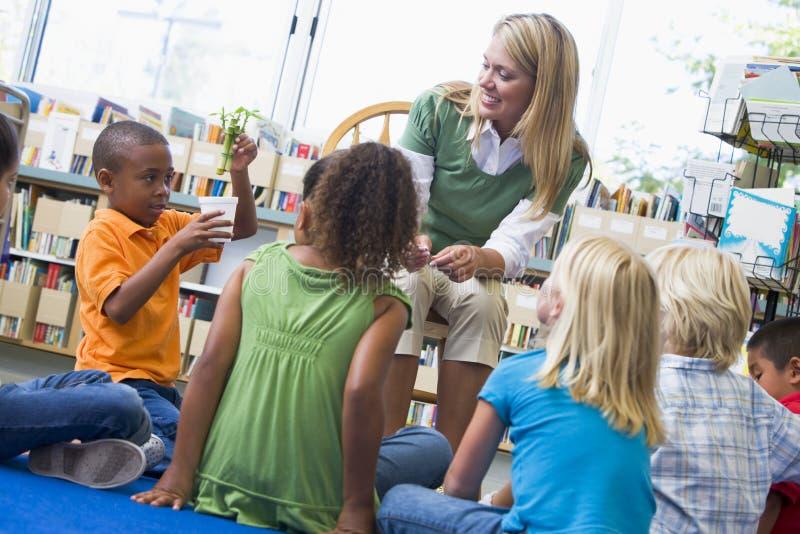 Profesor y niños que miran la planta de semillero imagen de archivo