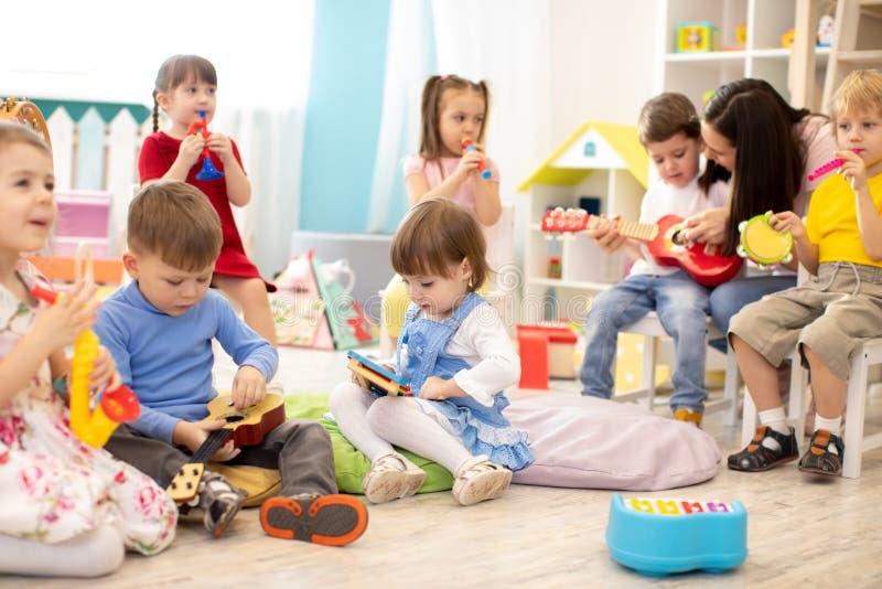 Profesora de guardería con niños en clases de música en guarderías. Los niños pequeños juegan juntos con juguetes musicales fotos de archivo libres de regalías