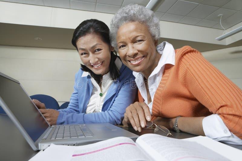 Profesores multiétnicos con el ordenador portátil y el libro en sala de clase imagen de archivo