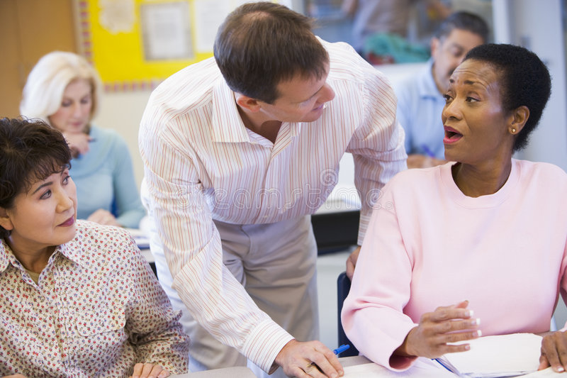 Professeur aidant l'étudiant mûr dans la classe photographie stock