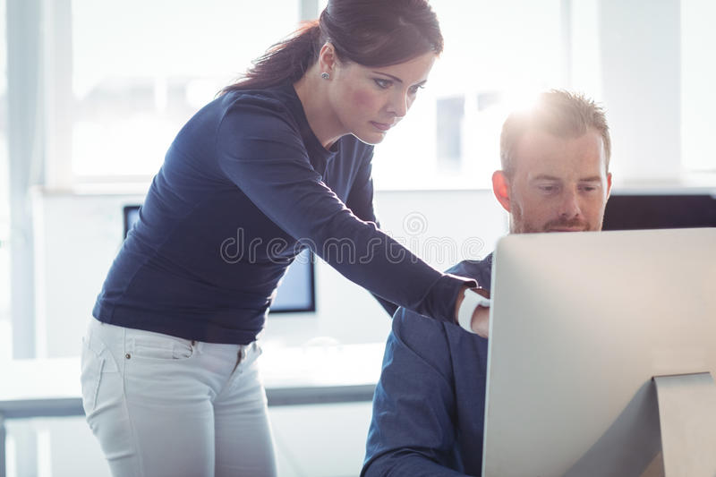 Professeur aidant l'étudiant mûr dans la salle des ordinateurs image libre de droits