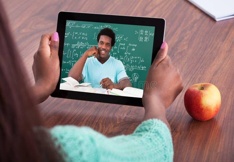 Professeur aidant l'étudiant par la vidéoconférence photographie stock