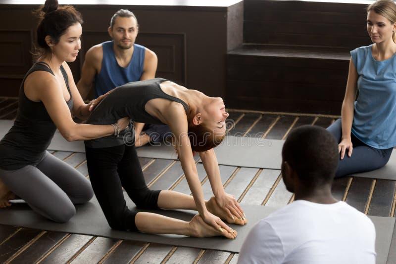 Professeur aidant la femme apprenant la nouvelle pose de yoga à la formation de groupe photo libre de droits