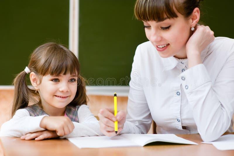 Professeur aidant la jeune fille avec la leçon d'écriture image libre de droits