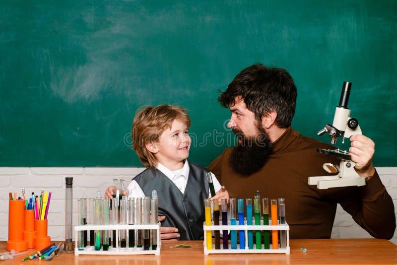 Professeur aidant le jeune gar?on avec la le?on Petit garçon gai et professeur de sourire ayant l'amusement contre le mur bleu pa photographie stock libre de droits