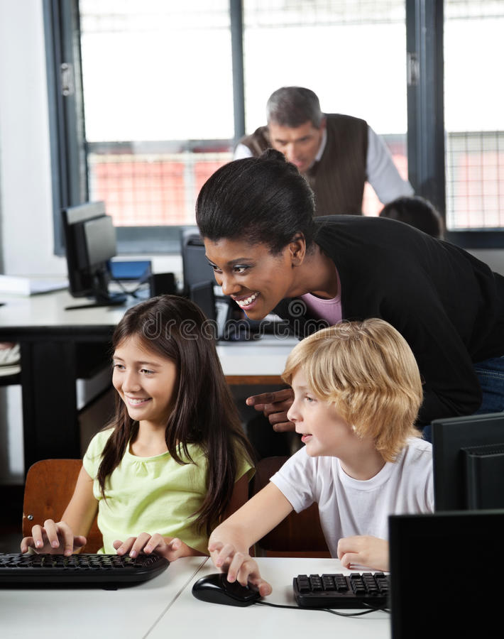 Professeur Assisting Schoolchildren In à l'aide du bureau photos libres de droits