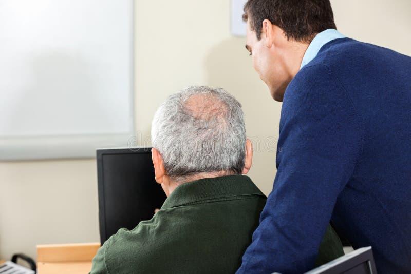 Professeur Assisting Senior Man dans la classe d'ordinateur images stock