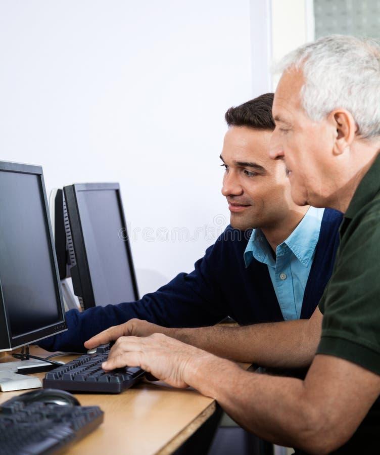 Professeur Assisting Senior Man en utilisant l'ordinateur photographie stock