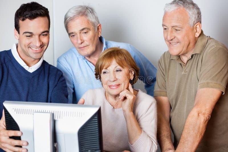 Professeur Assisting Senior People en utilisant l'ordinateur à la classe photos libres de droits
