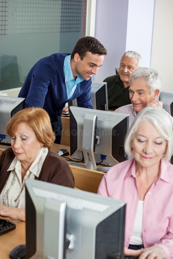 Professeur Assisting Senior Students dans la classe d'ordinateur photographie stock libre de droits