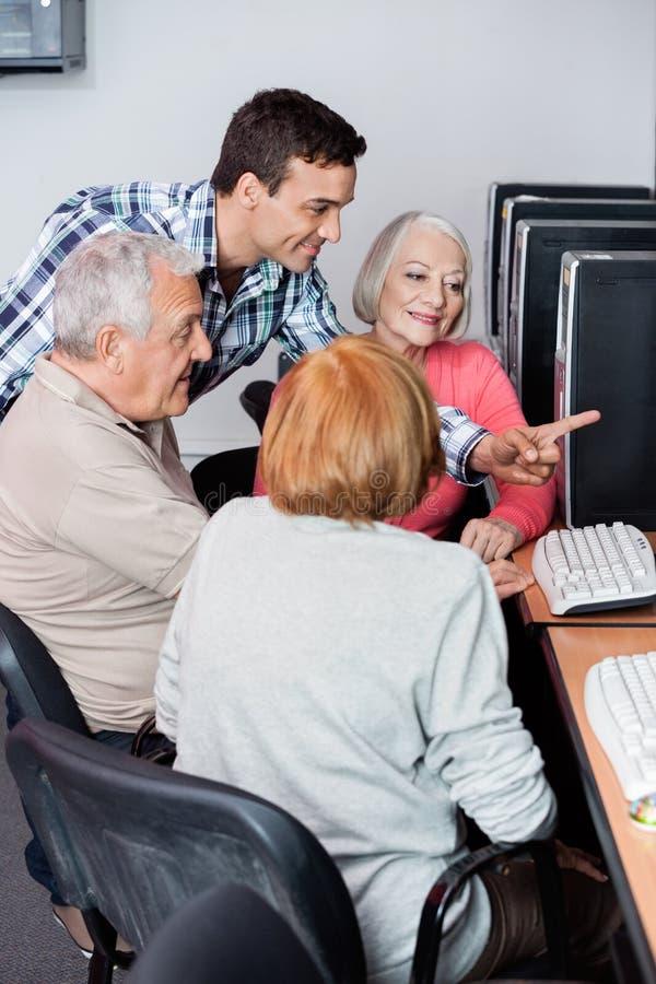 Professeur Assisting Senior Students en utilisant l'ordinateur à la salle de classe image stock